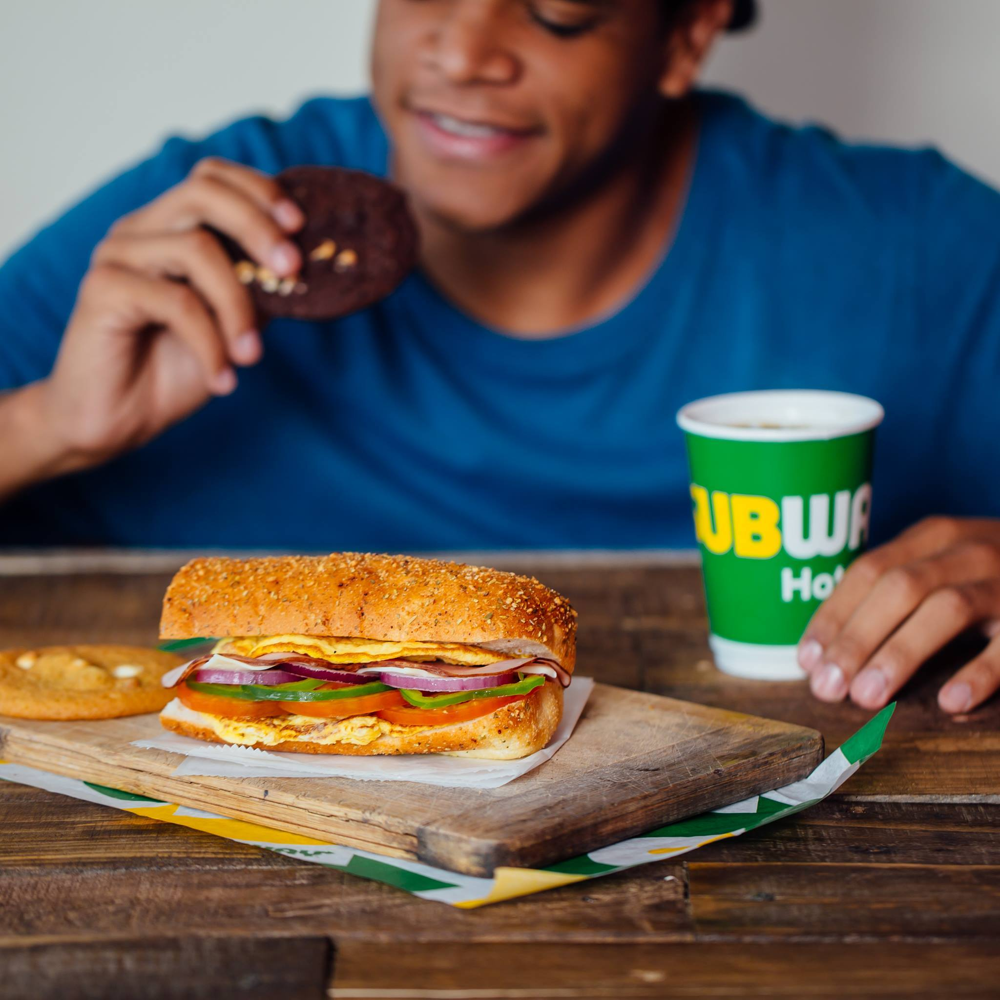 Man at Subway eating s Sandwich, cookie and drinking