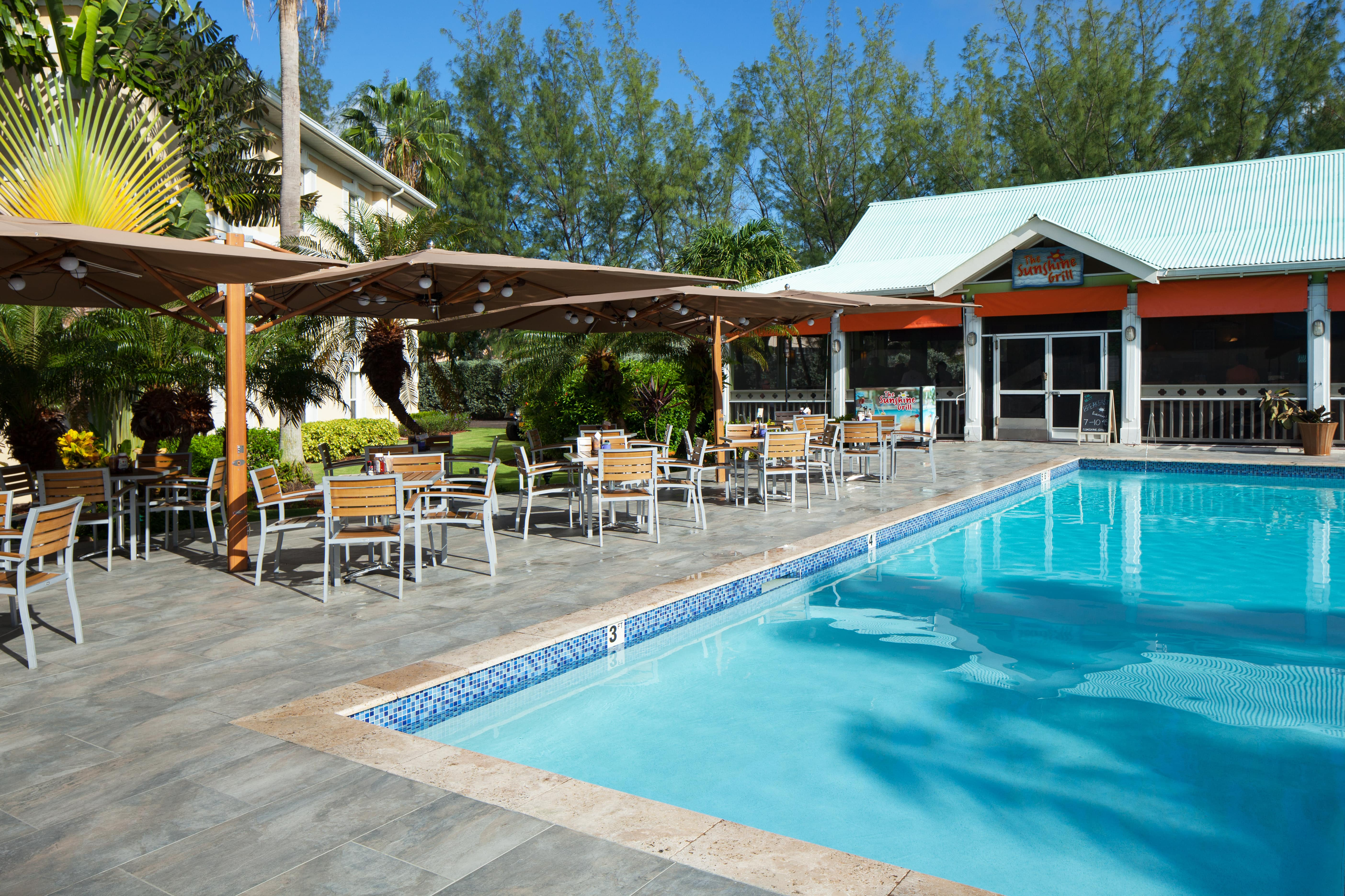 Sunshine Grill Cayman Outside pool and cahirs